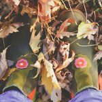 Overhead shot of a girl's rubber boots among fallen leaves.