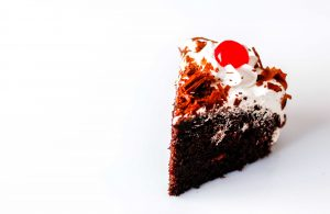 chocolate cake with a cherry and whipped topping.