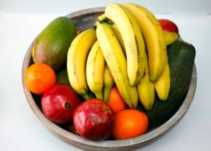 A bowl of fruit including bananas on a white background