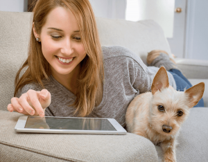 Young lady happily interacting with her tablet while holding a puppy.