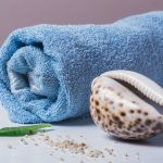 rolled blue towel and seashell