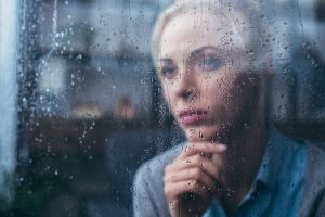 Sad woman looking out of a rain-soaked window
