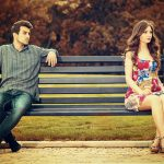 Young woman ignoring a man looking at her on a park bench