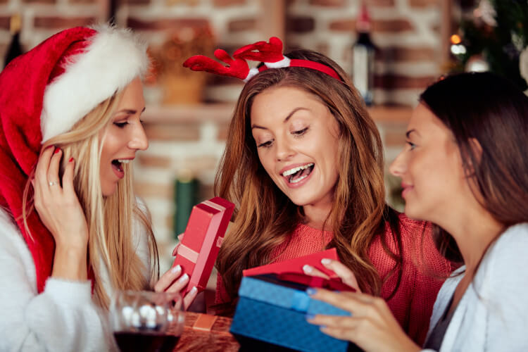 Three female friends swapping Christmas gifts