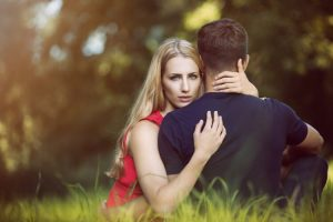 young couple embracing in the park grass