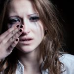 young lady crying and wiping away tears