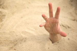 hand reaching out from beneath sand
